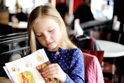 Little girl looking at a menu in cafe